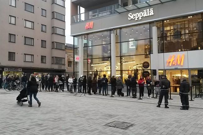 Över 50 personer köar inför öppningen av det nya köpcentret.